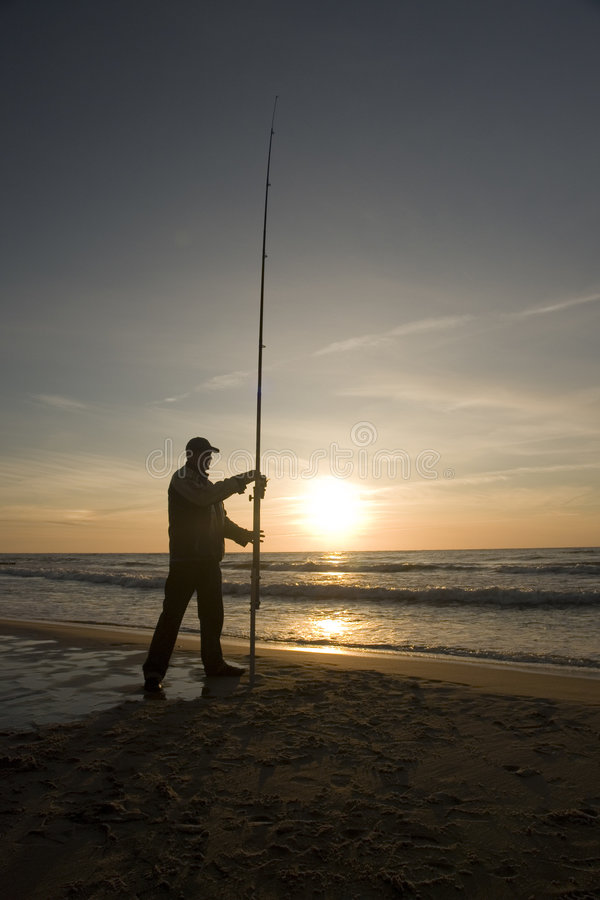 Silhouette of man fishing stock photography