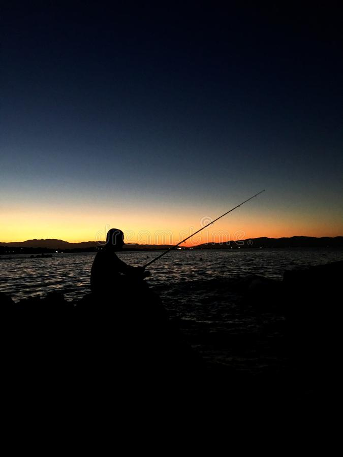 Silhouette of man fishing with fishing rod during sunset. Landscape, caucasian, freshwater, active, reel, pond, person, recreation, fisherman, sport, shore royalty free stock photography