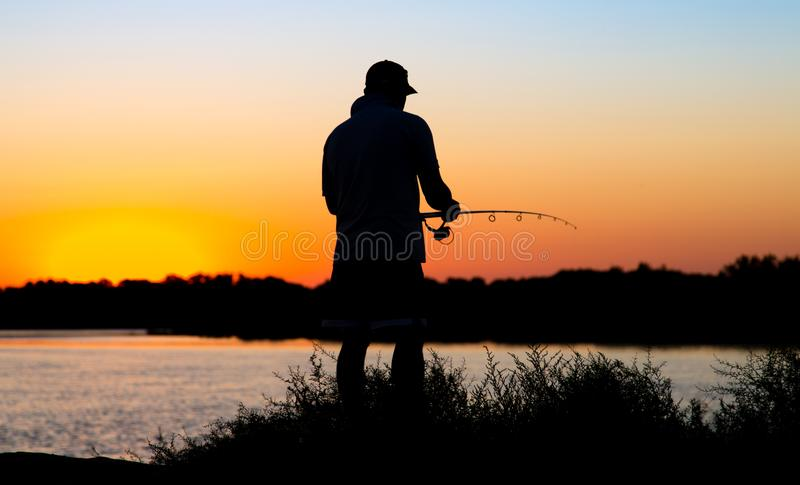 Silhouette of a man with a fishing rod at sunset stock photography