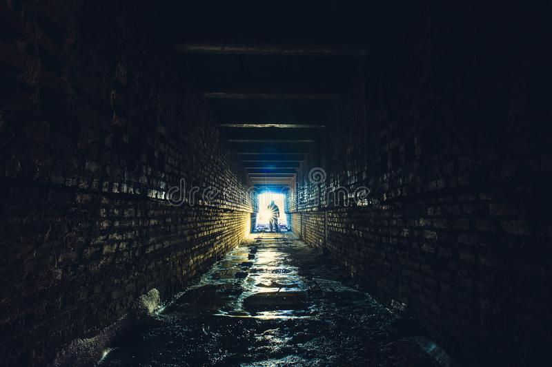 Silhouette of man with flashlight in dark dirty brick underground tunnel or sewerage corridor stock photography