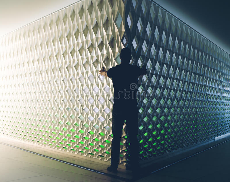 Silhouette of man in front of light and dark wall. Silhouette of man in front of light and dark modern architecture wall. Darkness versus light. Two sides to royalty free stock image