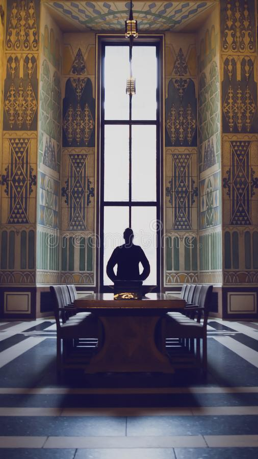 Silhouette of man in a grand hall stock photography