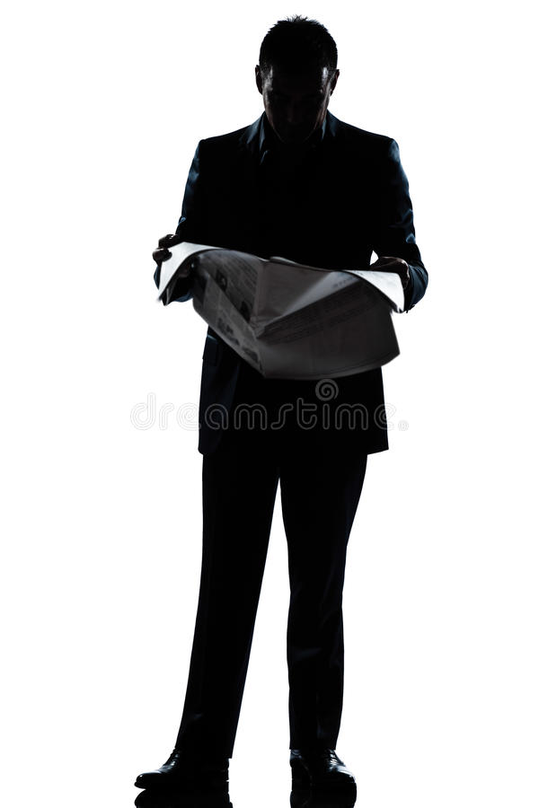 Silhouette man full length reading newspaper. One caucasian man standing reading newspaper full length silhouette in studio isolated white background stock images