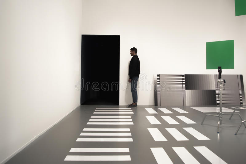 Silhouette of man among geometric objects in art exhibition room. royalty free stock photos