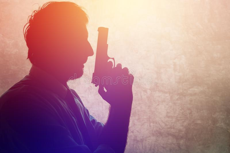 Silhouette of a man with a gun stock photo