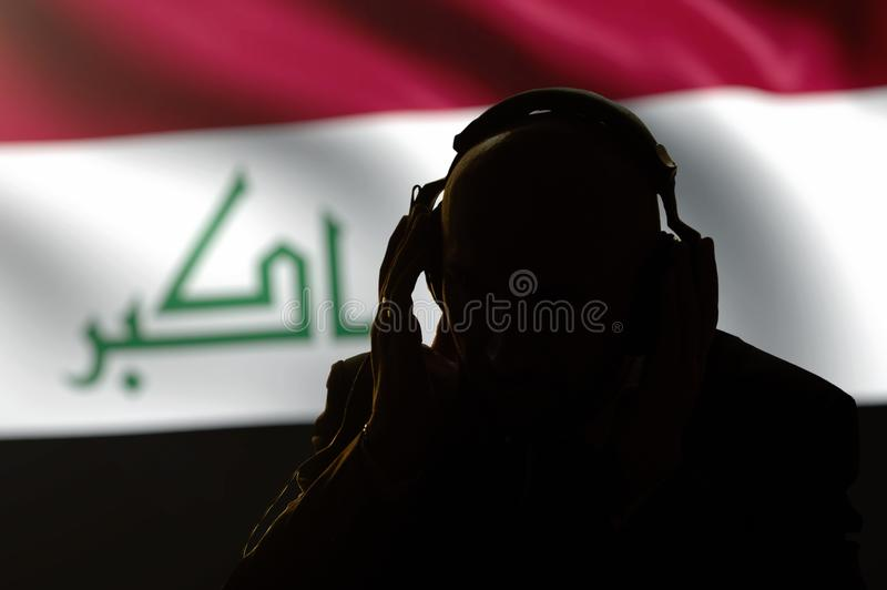 Silhouette of a man in headphones listening to a secret agent, spy and intelligence officer, the flag of Iraq, Internet control, b. Acklight royalty free stock images
