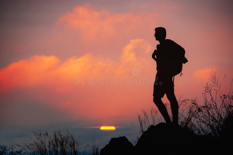 Silhouette of man hiker standing on rocky mountain peak with sunset golden sky feeling of freedom.  royalty free stock images