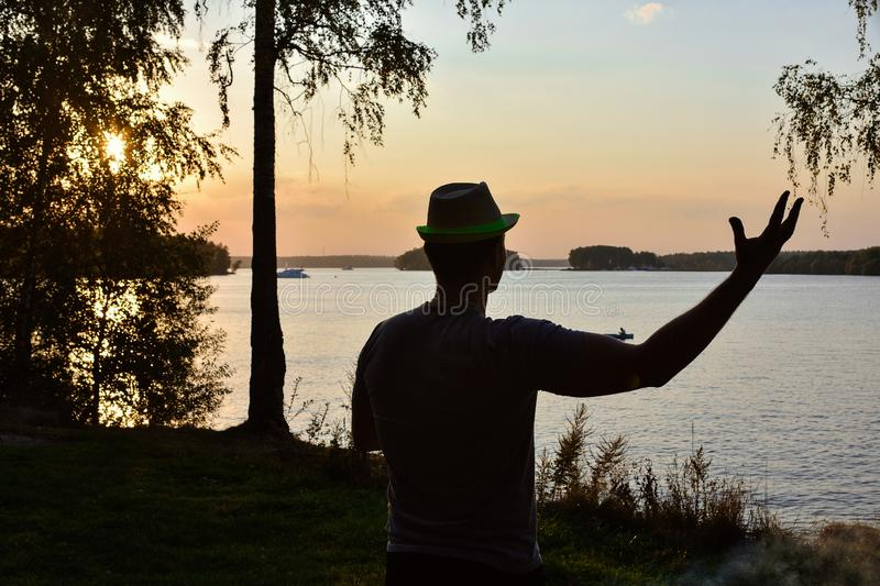 Silhouette of a man with his hand. Raised against the setting sun royalty free stock photo