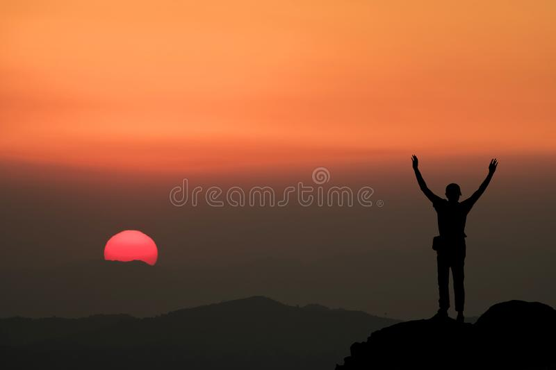 Silhouette of man hold up hands on the peak of mountain royalty free stock photos