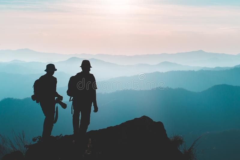 Silhouette of man hold up hands on the peak of mountain,success concept royalty free stock photos