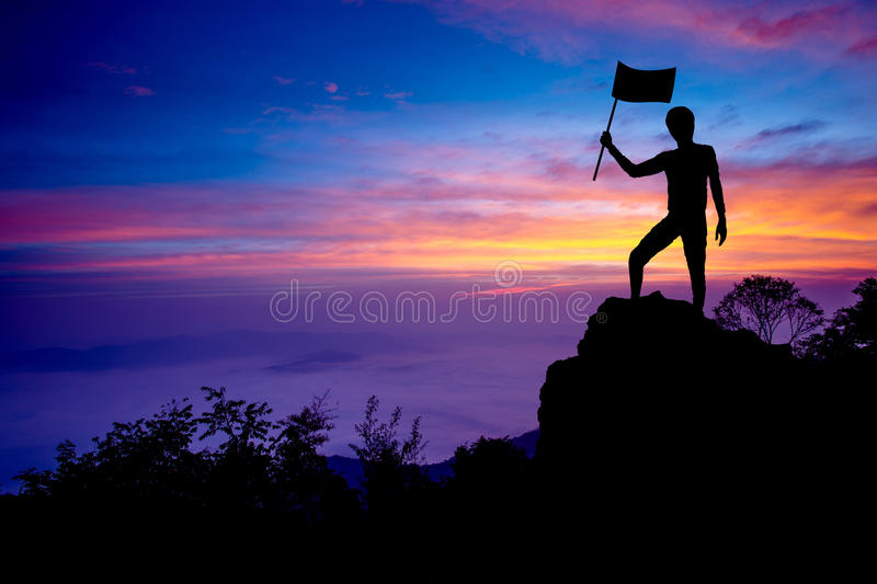 Silhouette of man holding flag standing on the mountain. With success stock photography
