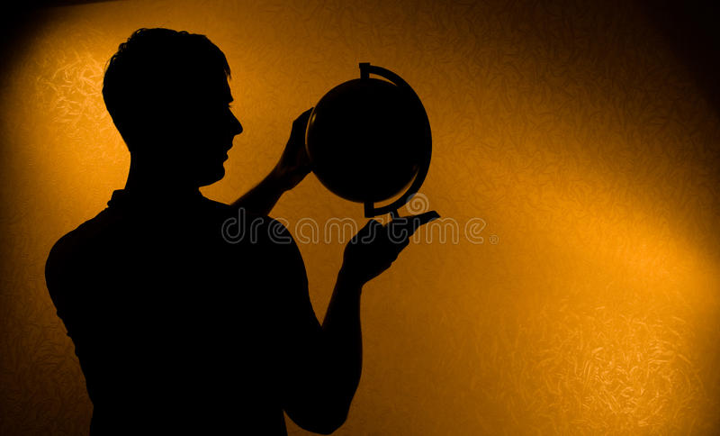 Silhouette of man holding globe. Your World - silhouette of man holding globe in the darkness royalty free stock photos