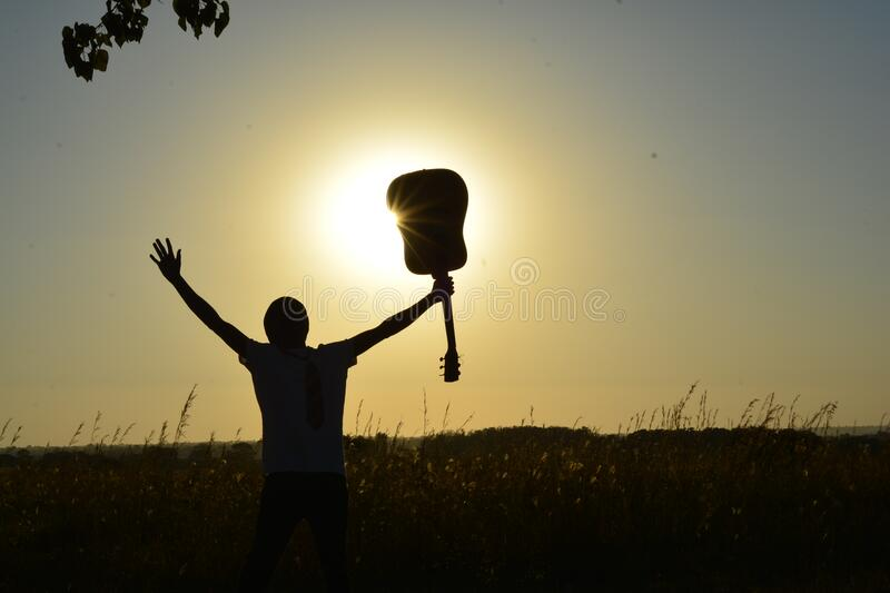 Silhouette of Man Holding Guitar on Plant Fields at Daytime stock photos