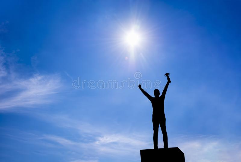 Man holding up a gold trophy cup royalty free stock photo