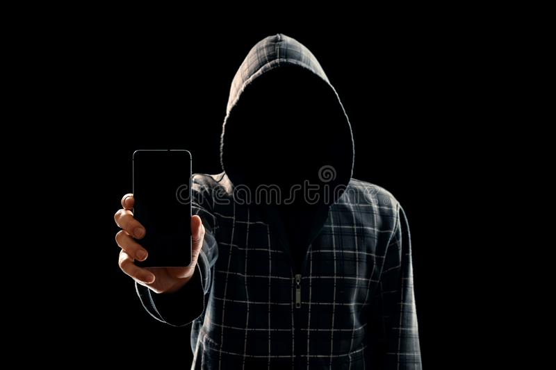 Silhouette of a man in a hood on a black background, his face is not visible, the hacker is holding the phone in his hands. The stock images
