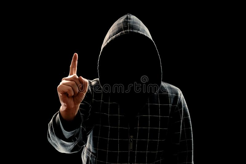 Silhouette of a man in a hood on a black background, his face is not visible, he lifts his finger up. The concept of a criminal, stock image