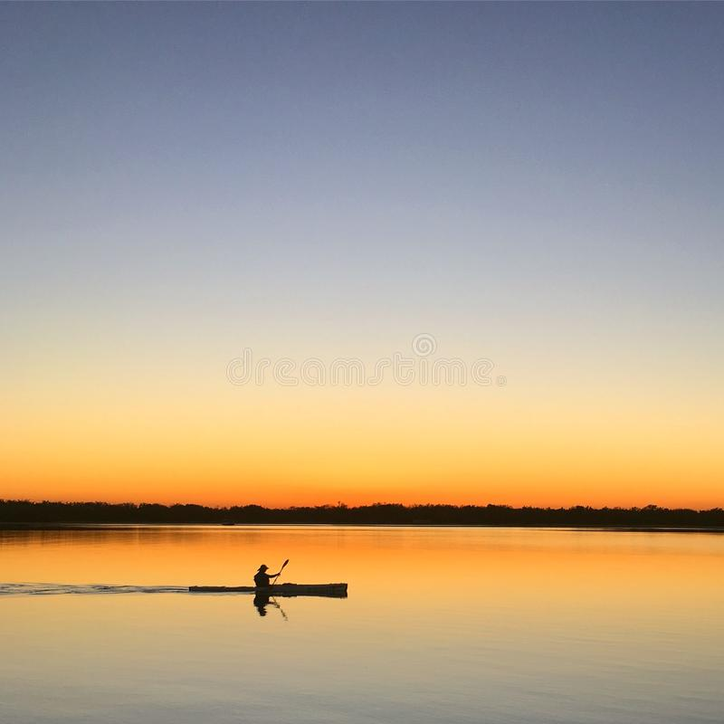 Silhouette of Man Inside of Boat Sailing on Body of Water during Sunset stock image