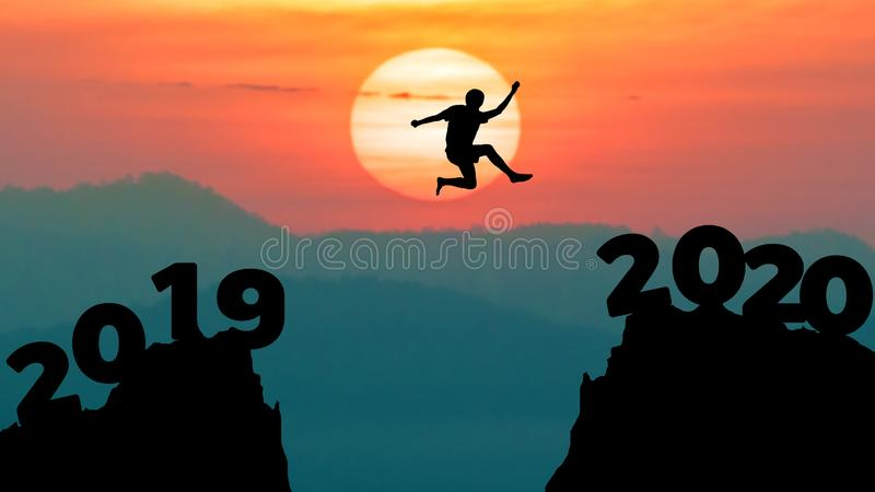 Silhouette man jump between 2019 and 2020 years. Happy new year 2020 concept for achievement stock photo