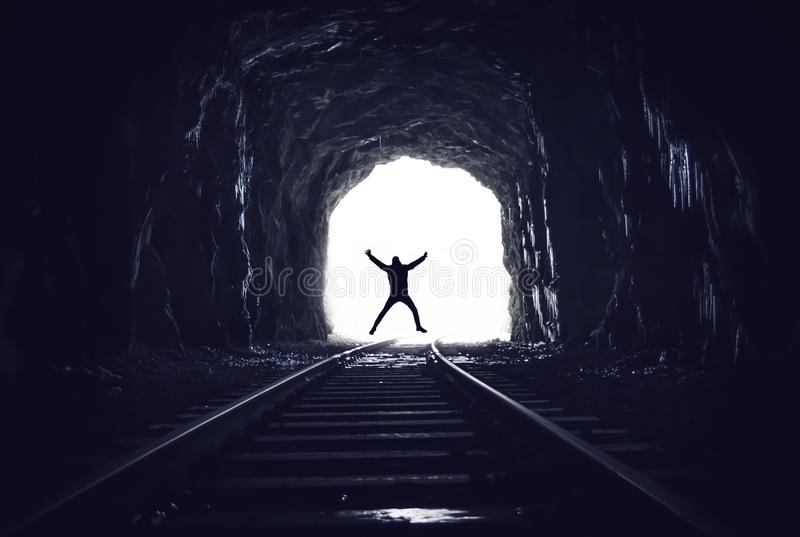 Silhouette of man jumping in abandoned railway tunnel. Silhouette of a man jumping in abandoned grotto like railway tunnel stock photos