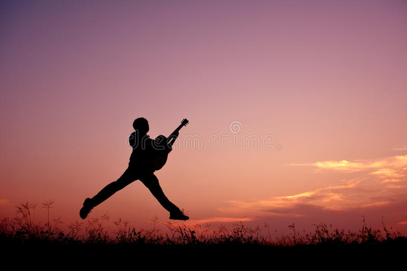 Silhouette man jumping with guitar royalty free stock photography