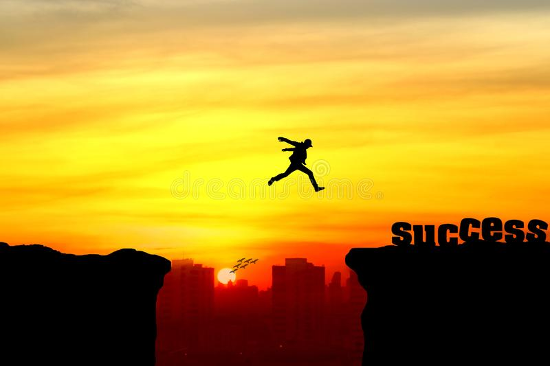 Silhouette of a man jumping over the cliff stock image