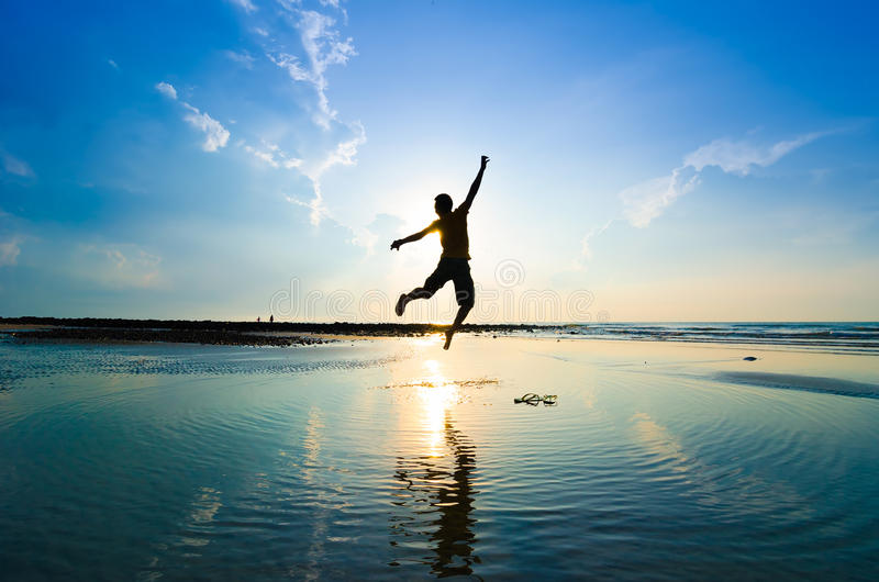 Silhouette of a man jumping over sun royalty free stock photo