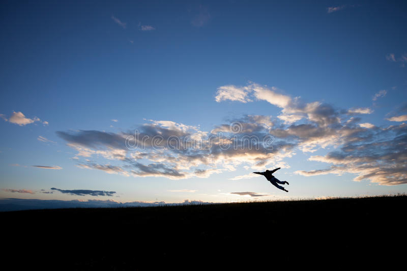 Silhouette of man jumping in sky. In front of blue sky royalty free stock photo