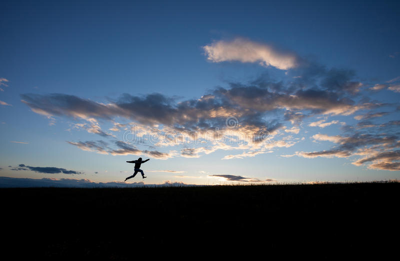 Silhouette of man jumping in sky. In front of blue sky royalty free stock photos