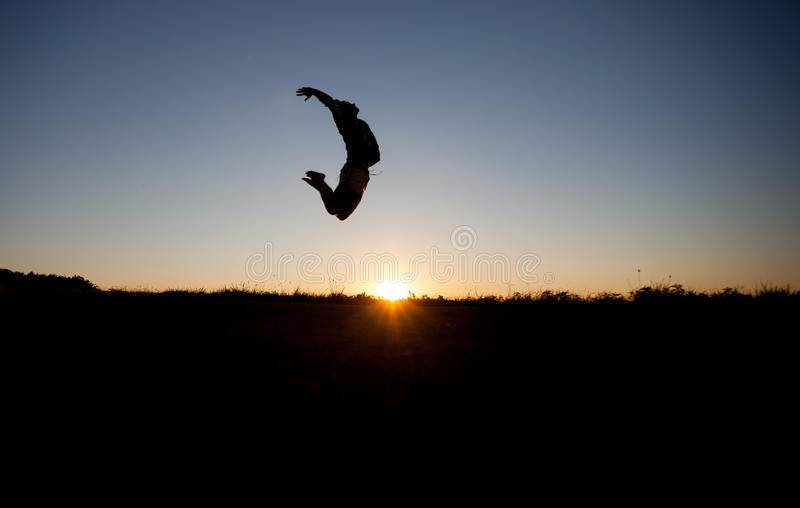Silhouette of man jumping. In sunset stock photography