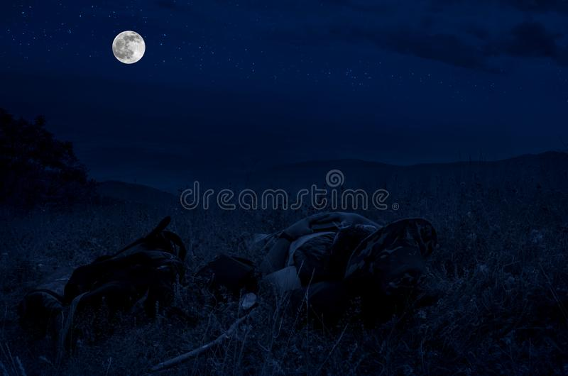 Silhouette of a Man lying on a grass at the top of the mountain and looking up against bright full moon and stars on night sky. Silhouette of a Man lying on a stock photos