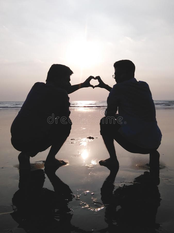 Silhouette of 2 Man Making Heart Sign royalty free stock photography