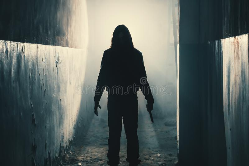 Silhouette of man maniac or killer or horror murderer with knife in hand in dark creepy and spooky corridor. Criminal robber stock image