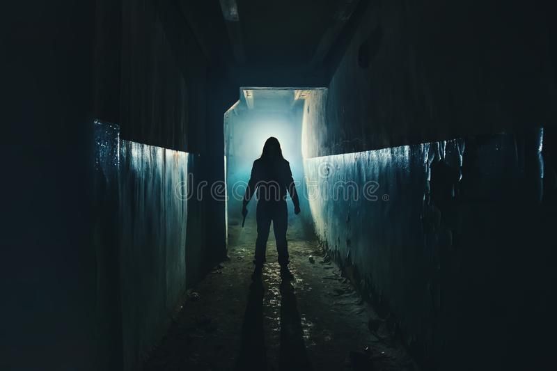 Silhouette of man maniac or killer or horror murderer with knife in hand in dark creepy and spooky corridor. Criminal robber stock photography