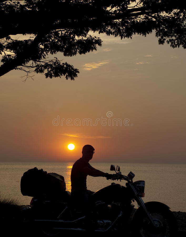 silhouette man on motorcycle stock photography