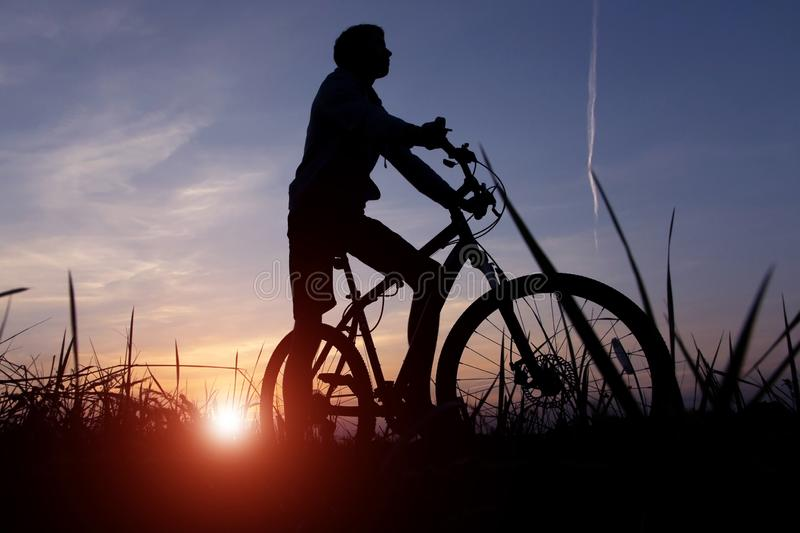 Silhouette of man on mountain bike, bicycle at sunset sky background with sun and sunlight royalty free stock photo