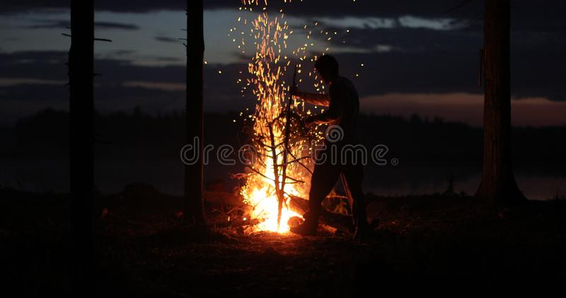 Silhouette of a man near the fire at night against the sky royalty free stock images