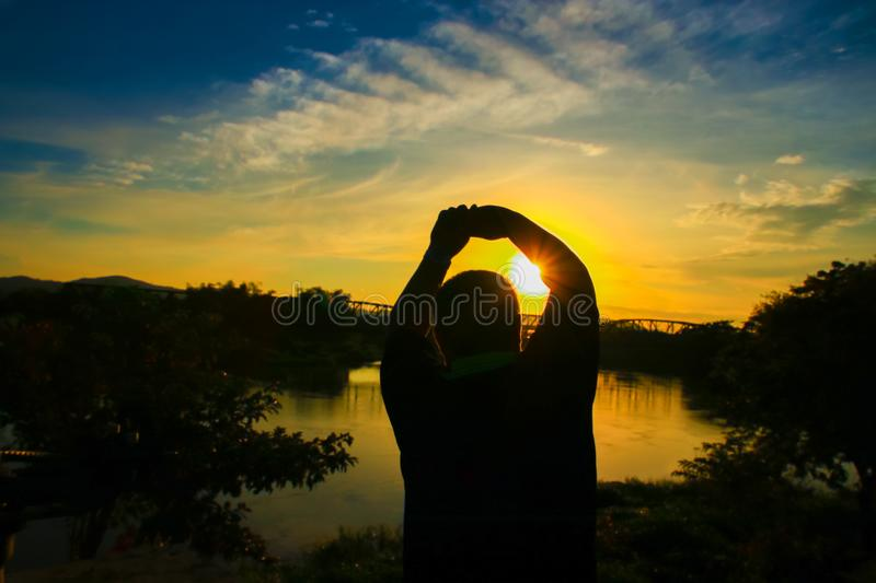 Silhouette of man obese exercise and yoga practicing in sunrise the morning with copy space stock photography