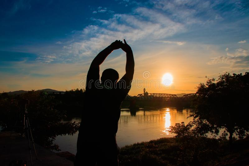 Silhouette of man obese exercise and yoga practicing in sunrise the morning with copy space royalty free stock photography