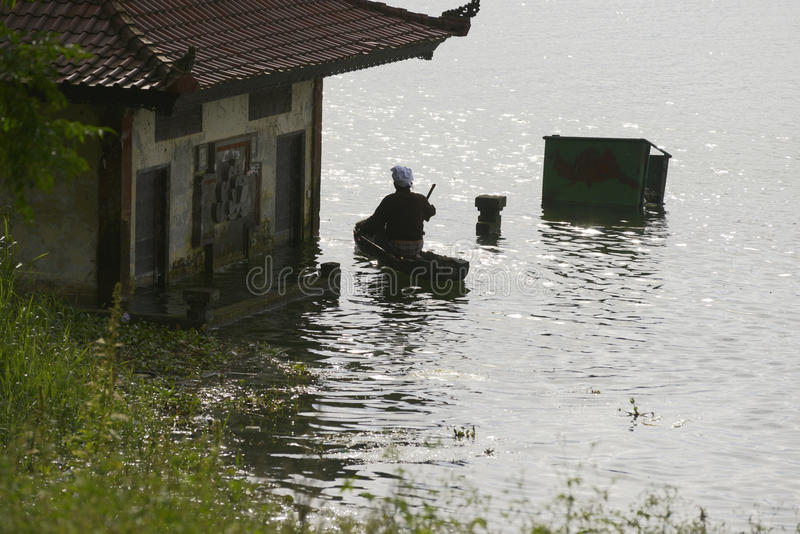 Silhouette of a man paddling toward a lakeside houses submerged stock image