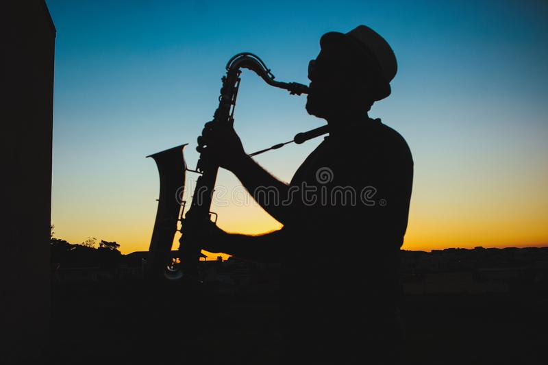 Silhouette of a Man Playing Saxophone during Sunset royalty free stock photo