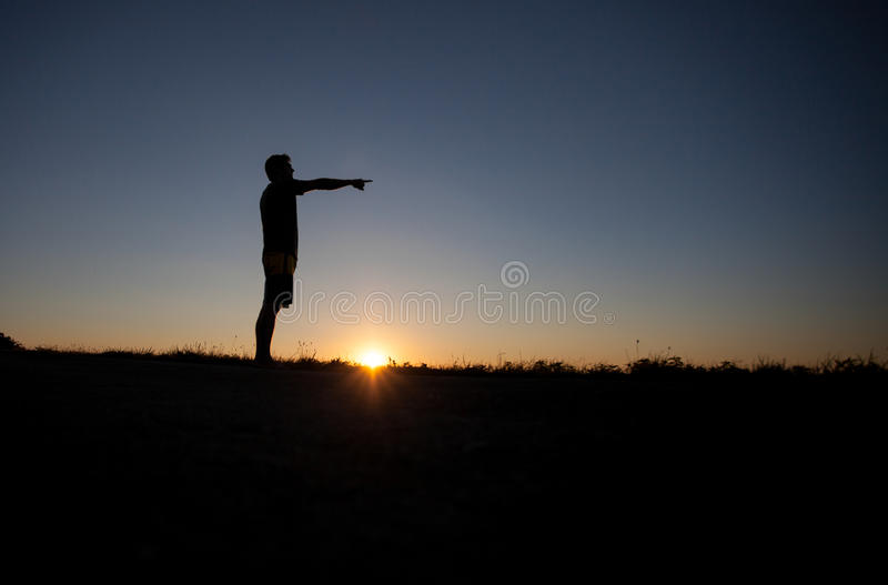 Silhouette of man pointing with finger. Silhouette of man standing in sunset and pointing with finger in right direction stock photos