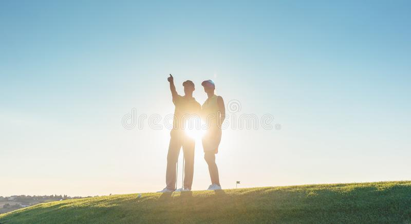 Silhouette of a man pointing while standing next to his partner stock image