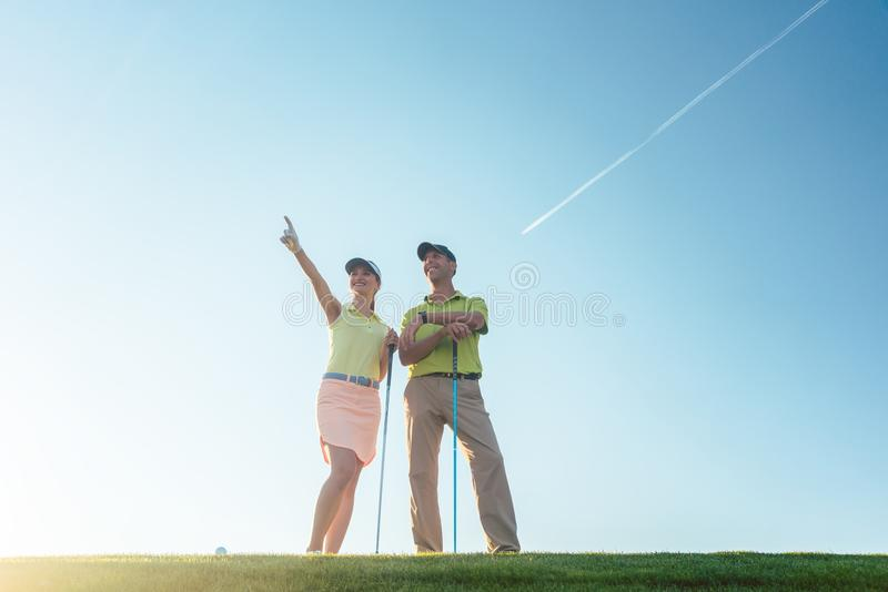 Silhouette of a man pointing while standing next to his partner royalty free stock photography