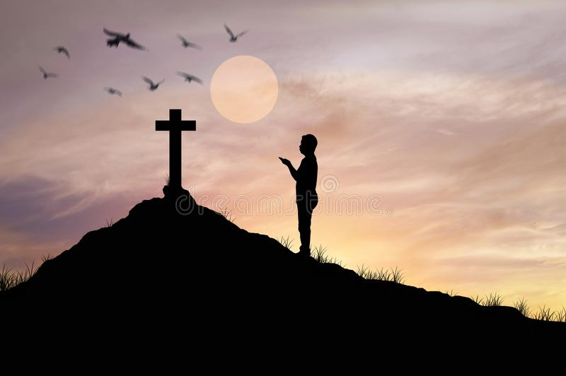 Silhouette man praying in front of cross with faith. And belief stock images