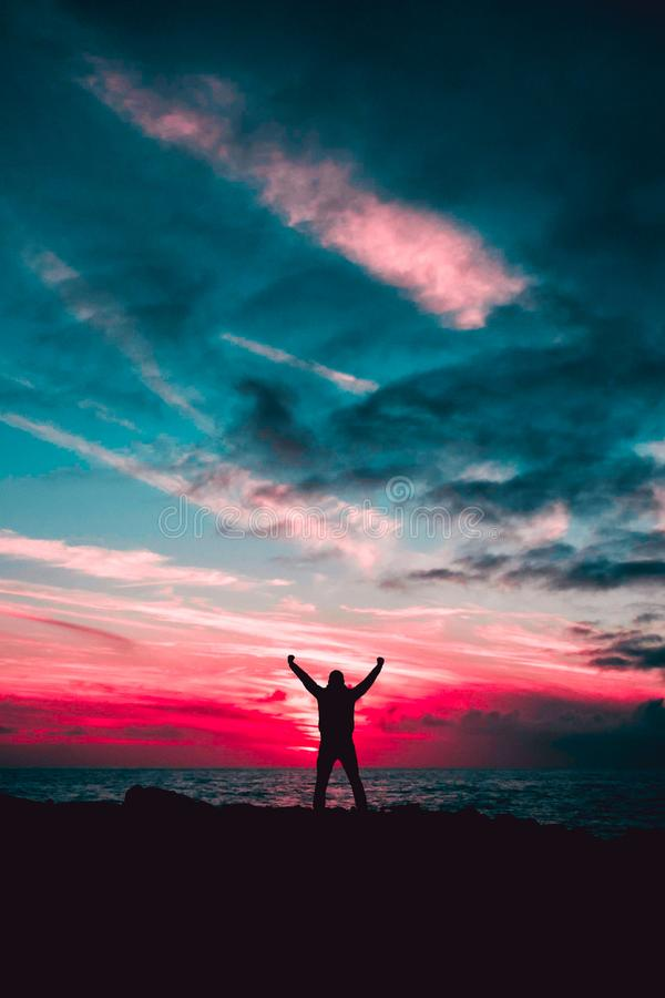 Silhouette of Man Raising Hands Against a Red Sunset Light Under Green Clouds royalty free stock photo