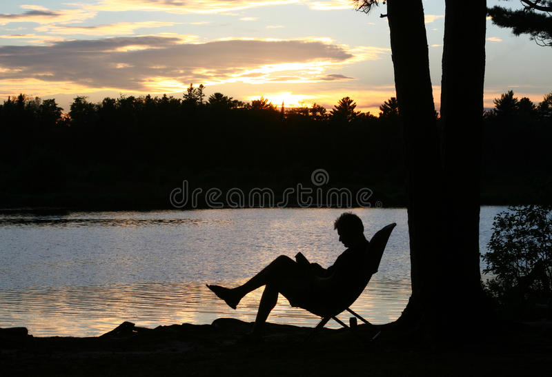 Silhouette of a man reading at sunset. The silhouette of a man reading by a lake at sunset royalty free stock image