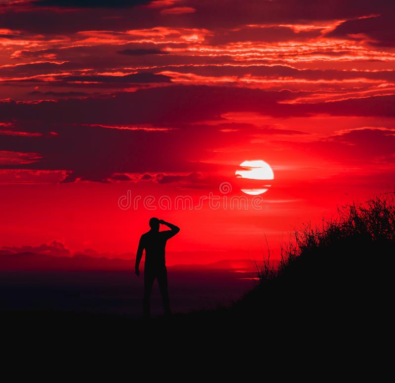 Silhouette of Man during Red Sun stock photo