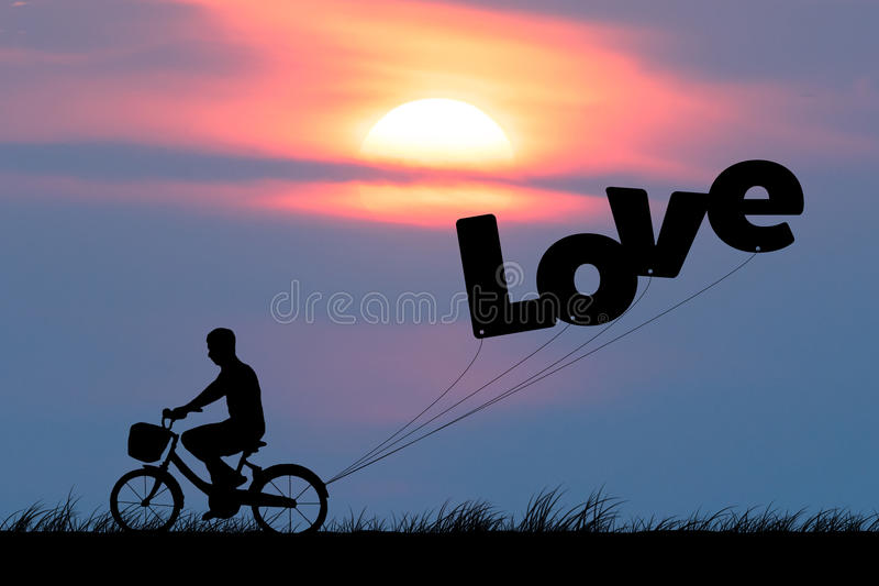 Silhouette of man ride on bicycle with air balloons for wording LOVE at sunset sky (Love valentine concept). Silhouette of man ride on bicycle with air balloons royalty free stock image