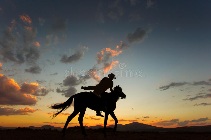 Silhouette of man riding a horse on sunset with beautiful background stock photos