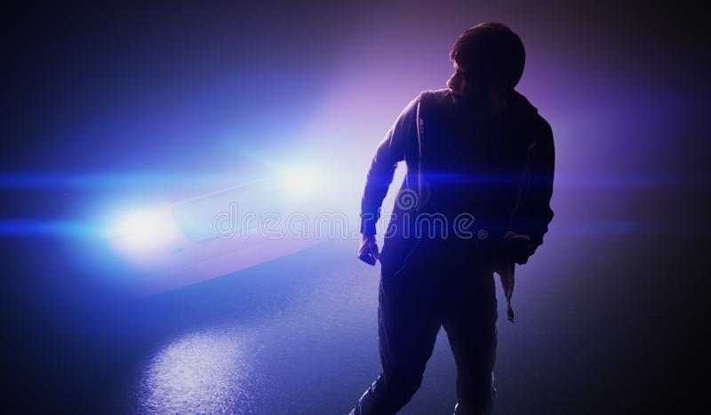Silhouette of man running away from car on road at night. royalty free stock photo